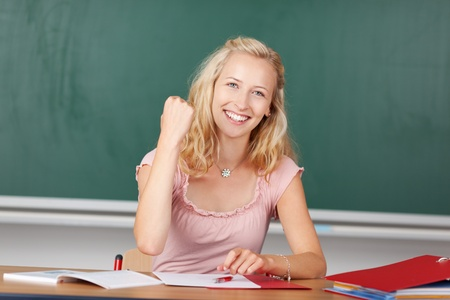 Portrait of happy young female teacher with clenched fist at classroom desk photo