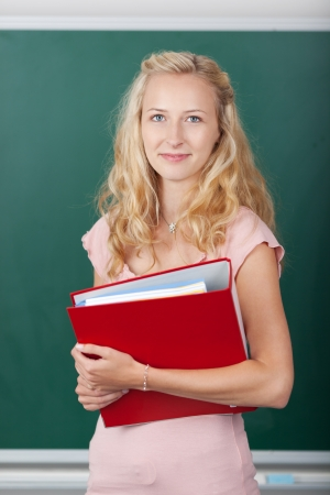 Portrait of beautiful female student holding binder against chalkboard Stock Photo - 21170562
