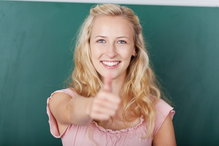 Portrait of young female student showing thumbs up sign at classroom Stock Photo - 21170582