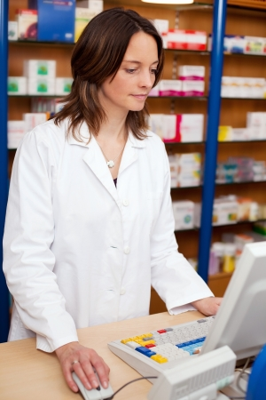 Mid adult female pharmacist using computer at pharmacy counter Stock Photo - 21171158