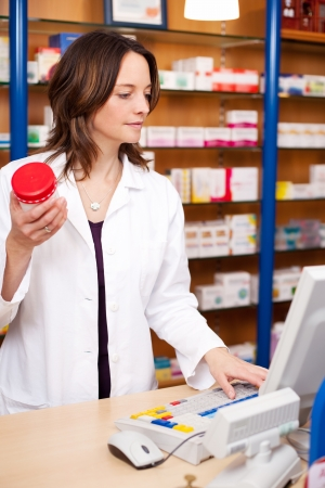 Mid adult female pharmacist holding pill bottle while using computer at pharmacy counter Stock Photo - 21171163