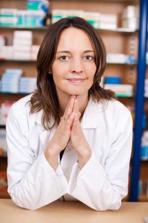 Portrait of confident female pharmacist with hands clasped leaning on pharmacy counter photo