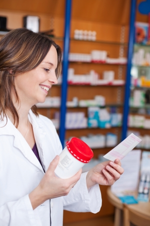 Mid adult female pharmacist holding medicine bottle while reading prescription paper in pharmacy photo