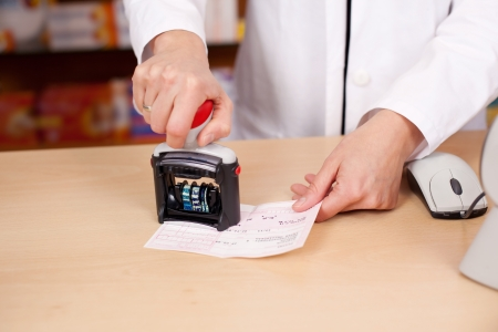 Midsection of female pharmacist stamping bill at pharmacy desk photo