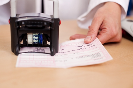 stamping: Female pharmacist stamping Prescription at pharmacy desk Stock Photo