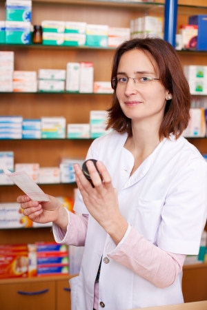 Portrait of young female pharmacist holding medicine bottle against shelves in pharmacy Stock Photo - 21171183
