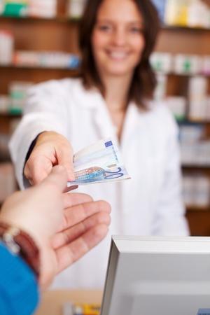 paying money: Customers hand passing money to female pharmacist in pharmacy