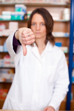 Portrait of mid adult female pharmacist showing thumbs down sign photo