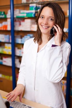 mid adult female: Mid adult female pharmacist using cordless phone at pharmacy desk