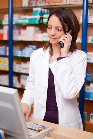 Female pharmacist using cordless phone at pharmacy desk Stock Photo - 21171272