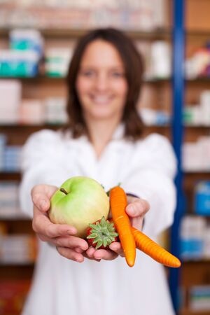 Portrait of mid adult female pharmacist holding artificial carrots; strawberry and apple at pharmacy photo