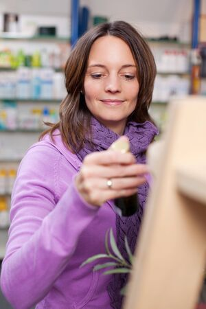mid adult female: Mid adult female customer looking at pill bottle in pharmacy