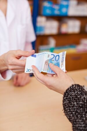 Closeup of customers hand paying money to pharmacist at counter photo