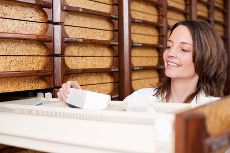 stockroom: Mid adult female pharmacist searching medicines at stockroom