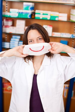 mid adult female: Portrait of mid adult female pharmacist holding mask with smiley in pharmacy