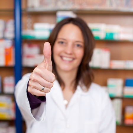 Portrait of confident female pharmacist showing thumbs up sign at pharmacy photo