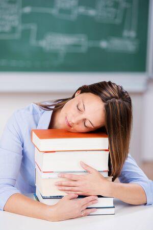 Mid adult female teacher sleeping on stack of books at classroom desk photo