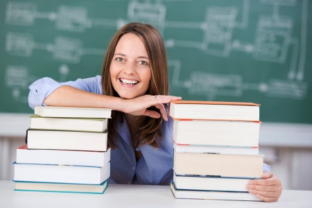 mid adult female: Smiling mid adult female teacher with two stack of books at classroom desk Stock Photo