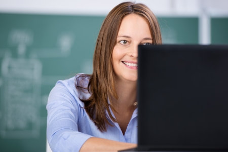 Mid adult female teacher using laptop against chalkboard in classroom Stock Photo - 21175920