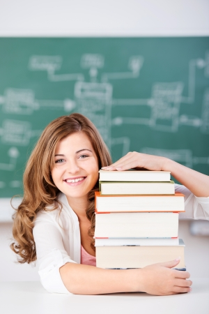 Portrait of happy female student with stack of books at table in classroom photo