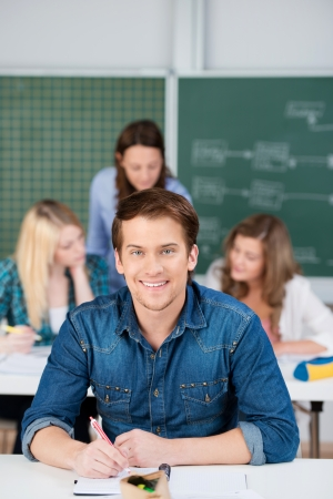 Portrait of young male student writing at desk with female classmates and teacher in background Stock Photo - 21175933