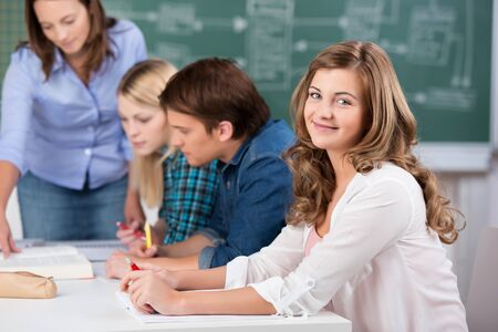 Portrait of beautiful teenage girl smiling with teacher assisting classmates at classroom desk photo
