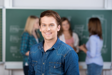 Portrait of young male student smiling with teacher and classmates in background photo