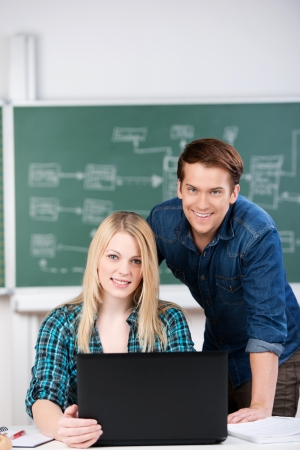 computer science class: Portrait of confident male and female students with laptop at desk