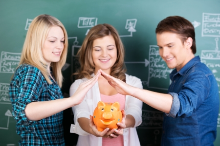 scholarship: Teenage girl holding piggybank while friends protecting it against chalkboard in classroom