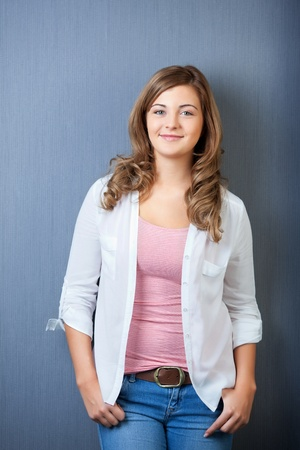 hand in pocket: Portrait of teenage girl wearing casuals isolated over blue background