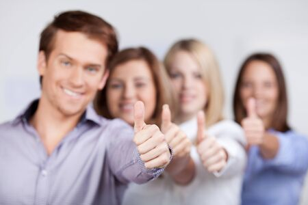 Young businessman and businesswomen showing thumbs up sign in office photo