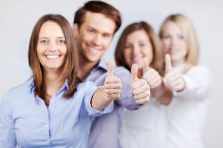 alright: Businesswomen and businessman showing thumbs up sign in office Stock Photo