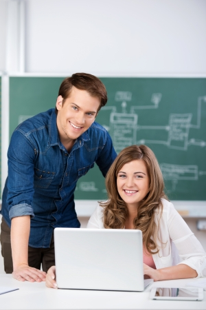 Happy male and female students with laptop at classroom desk photo