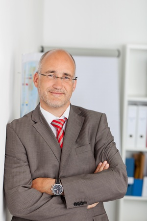Portrait of confident mature businessman leaning on wall at office photo