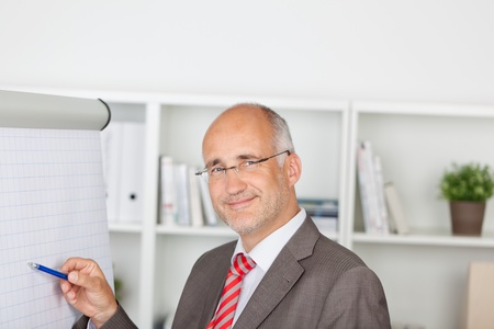 1 mature man: Portrait of confident mature businessman pointing at flipchart in office Stock Photo
