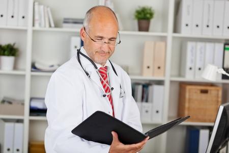 waistup: Mature male doctor reading folder against shelves in office