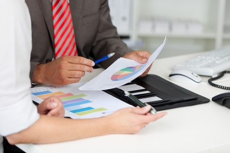 Midsection of businessman and businesswoman with graphs at office desk photo