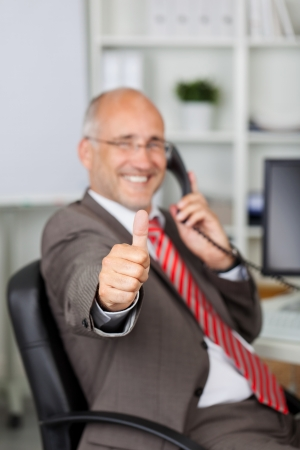 landline phone: Portrait of mature businessman gesturing thumbs up while using landline phone in office