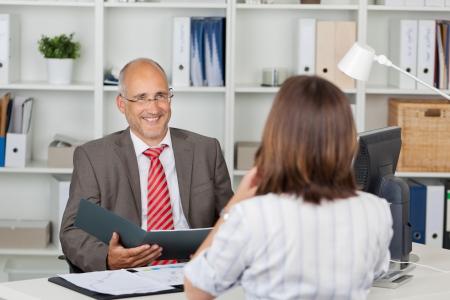 cv: Coppia uomo d'affari in possesso di curriculum di candidati donna alla scrivania in ufficio