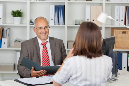 cv: Mature businessman holding CV of female candidate at office desk