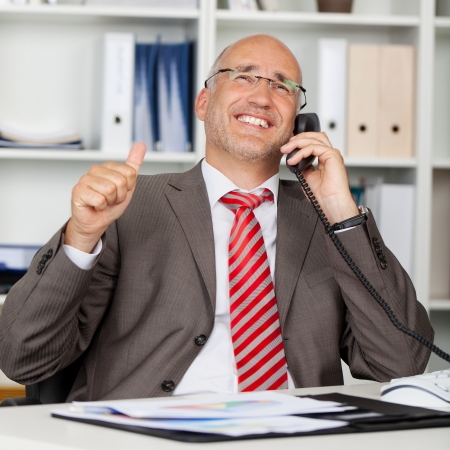 Happy mature businessman using landline phone while gesturing thumbs up at office desk photo