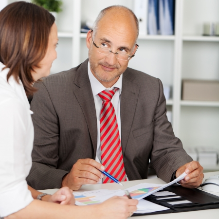 businessman looking at female colleague in meeting photo