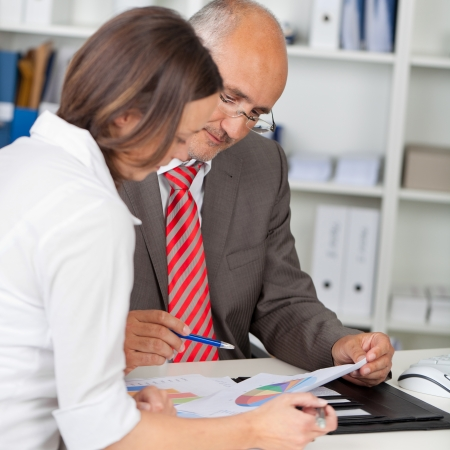 explain: Mature businessman and businesswoman with graphs in meeting at office desk