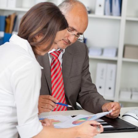 Volwassen zakenman en zakenvrouw met grafieken in de vergadering op het kantoor bureau