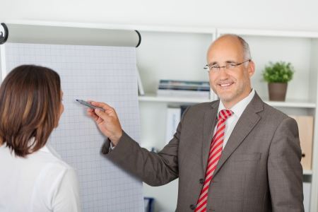 businessman in meeting pointing pen on flipchart photo