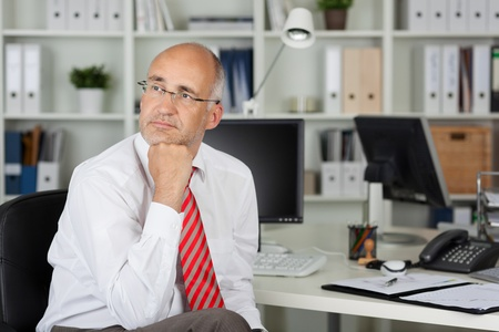 contemplative: employee with hand on chin looking to side in thought Stock Photo
