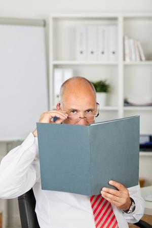 controling: Mature businessman peeking over file in office