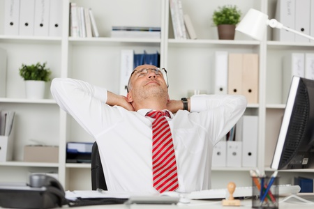 Relaxed mature businessman with hands behind head at office desk photo