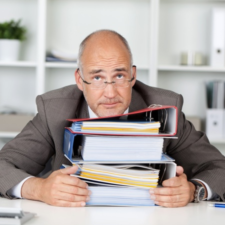 workload: overworked businessmann leaning head on a stack of binders