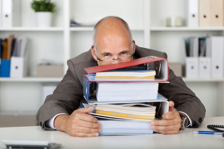 workaholic: businessman looking smiling over a stack of binders
